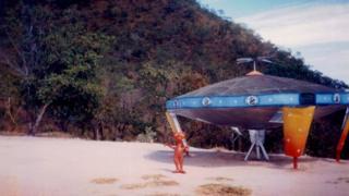 Discoporto de Barra do Garças, em Mato Grosso - uma escultura simulando uma espaçonave com um boneco representando um ET na cor laranja
