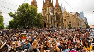 A huge, packed crowd at a junction in the centre of Melbourne city