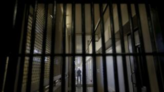A guard stands behind bars at a prison
