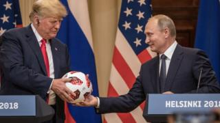 President Vladimir Putin hands President Donald Trump a World Cup football during a joint press conference after their summit on July 16, 2018 in Helsinki, Finland