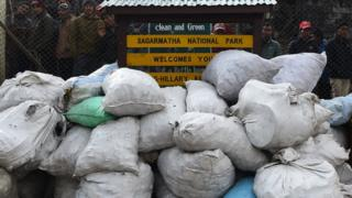 "Locals look at piles of rubbish bags lying against an airport fence next to a sign reading ""clean and green: Sagarmatha National Park Welcomes You"""
