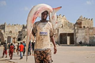"""A Somali fisherman whose T-shirt aptly reads """"Extra Large"""" carries a shark on his shoulder to the Hamarweyne fish market near the port in Mogadishu."""