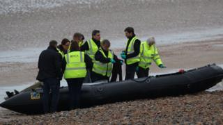 National Crime Agency officers examine the abandoned dinghy