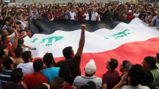 Protesters chant anti-Iraqi government slogans as they carry a large national flag during a protest against against corruption and the lack of government services in Tahrir Square in central Baghdad, Iraq, Friday, 31 July 2015