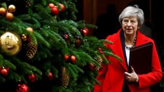 Theresa May walks past a Christmas tree as she leaves 10 Downing Street