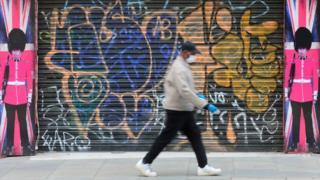 Man wearing face mask walking past boarded shop
