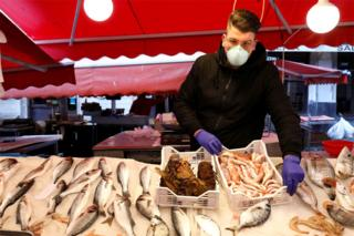 A man wearing a face mask next to a fish market stall