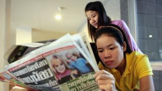 Resepsionis membaca koran dengan sampul kasus JonBenet Ramsey