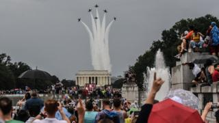 People react to a military flyover while President Donald Trump gives his speech during Fourth of July festivities in 2019
