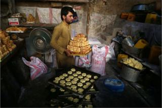 Afghans prepare biscuits at a factory ahead of the Muslim Festival of Eid al-Fitr, to mark the end of Ramadan, in Jalalabad, Afghanistan, 13 June 2018