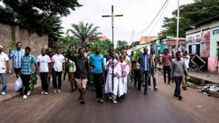 A man holds a cross as he takes part, with a group of Catholic faithfuls, in a demonstration outside the St Francois De Sales Church on 25 February 2018