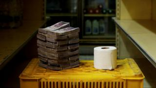 Rollo de papel higiénico junto a 2.600.000 bolívares.
