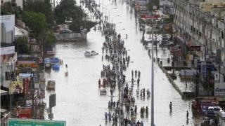 People walk through a flooded street in Chennai, India, Thursday, Dec. 3, 2015