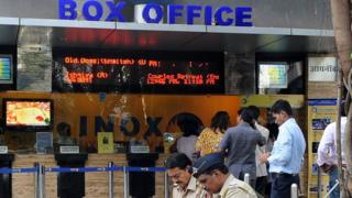 Policemen sitting outside a movie hall in India