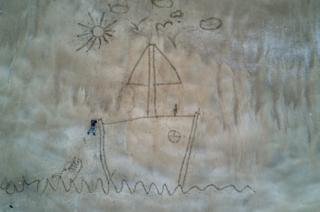 An image created in the sand representing Ugo in difficulty in the open sea