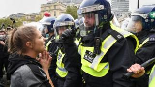 "Protesters and police at a ""We Do Not Consent"" rally at Trafalgar Square in London"