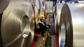 A worker inspects rolls of steel