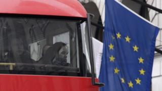 Passengers look out from a London bus as it passes an European Union flag in London.