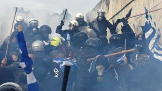 Demonstrators, including many in masks and helmets, clash with police
