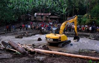"An excavator removes debris from the banks of the Sume river on October 12, 2018, after it burst its banks in the eastern village of Nanyinza, in Uganda""s Bududa district. - At least 34 people were killed after the river in eastern Uganda burst its banks, sending thick sludge and rocks barrelling into homes, disaster officials said"