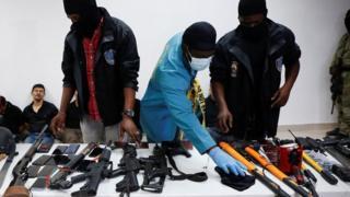 Гаити полициясы кармалгандардын куралдардын медиага көрсөтүп жатат