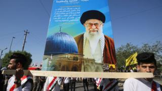 Iraklı Şii Müslüman gençler, Uluslararası Kudüs Günü'nde Bağdat'ta İran'ın dini lideri Ayetullah Ali Hameney'in fotoğrafının olduğu bir afiş taşıyor