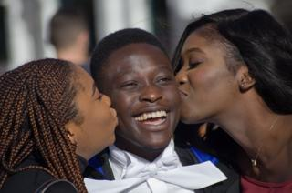 Two women kiss a boy on the cheeks at Cambridge University.