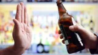 Una mano rechazando una botella
