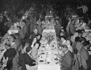 Large groups of people at tables in a hall