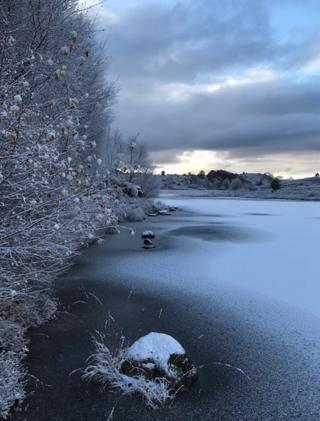 A frozen river with snow on top