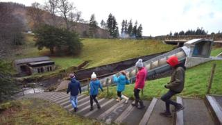 Visitors by the Archimedes screw hydro-electric turbine at Cragside, Northumberland