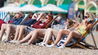 sports A group of women sit in the sunshine on the beach in Brighton, Britain