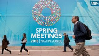 People walk past the IMF headquarters during the 2018 spring meetings of the International Monetary Fund and World Bank in Washington