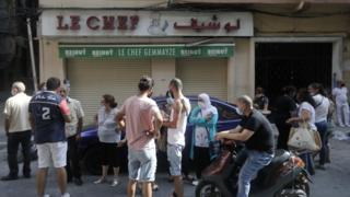 People stand outside the shuttered Le Chef restaurant on 13 August 2020