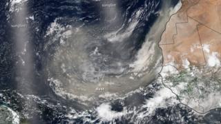 Imágen satelital que muestra una nube amarilla de polvo que proviene del oeste de África y cruza el Océano Atlántico