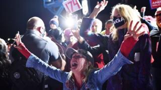 Una mujer con los brazos abiertos en celebración en acto de campaña de Trump en Mosinee.