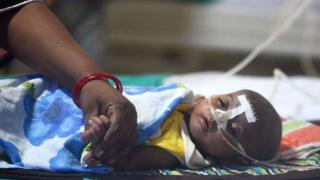 An Indian woman holds her child's hand at the encephalitis ward of the the Baba Raghav Das Hospital in Gorakhpur, in the northern Indian state of Uttar Pradesh, on August 14, 2017