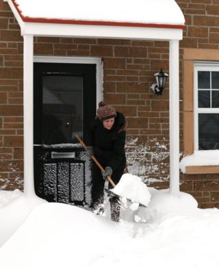 A woman clears snow from a doorway