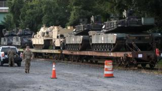 Two M1A1 Abrams tanks and other military vehicles sit on guarded rail cars at a rail yard on July 2, 2019 in Washington, DC