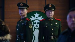 Paramilitary police officers stand guard near a Starbucks cafe in Beijing Railway Station in Beijing.