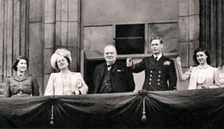 King George VI, Winston Churchill and the royal family wave to crowds from Buckingham Palace