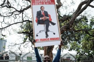 "A supporter holds a banner bearing a picture of President Uhuru Kenyatta as they celebrate on November 20, 2017 in Nairobi after Kenya""s Supreme Court dismissed two petitions to overturn the country""s October 26 presidential election re-run, validating the poll victory of Kenyatta."
