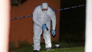 Forensic officers examine the scene of the shooting