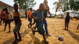 Young boys who just received a vaccine against cholera play football in Harare, Zimbabwe, on 5 October 2018