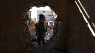 A rebel fighter stands near a hole in the wall as he carries his weapon on the outskirts of Al-Bab town in Syria