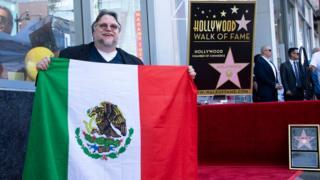 Guillermo del Toro con la bandera mexicana en el Paseo de la Fama.