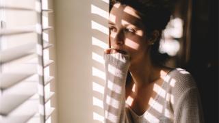 Mujer temerosa frente a la ventana