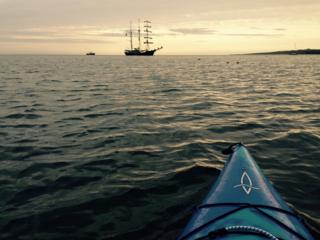 Kayak and tall ship