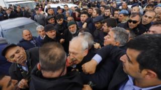 Kemal Kilicdaroglu being jostled by crowds at a funeral