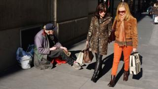 Women walk by a panhandler along Madison Avenue, one of Manhattan's premier shopping along with residential streets on November 1, 2011 in brand new York City.